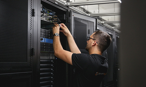 Collaborateur de DEVENSYS en train de cabler des serveurs dans un data center